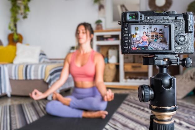 Giovane donna che si esercita a casa facendo pilates e registrando a lei con la fotocamera digitale per insegnare l'allenamento e produrre il concetto di persone di stile di vita sano gratuito di creatore di contenuti di classe web