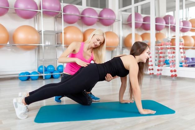 Giovane donna che si esercita con il suo istruttore di fitness