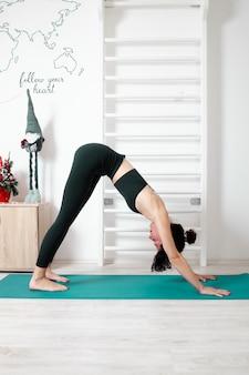 Giovane donna che esercita yoga nel suo appartamento e godersi la sua giornata
