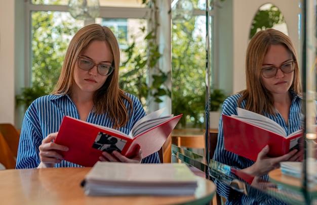 Giovane donna in occhiali che legge un libro in una caffetteria moderna con piante e lettore di luce diurna nella caffetteria