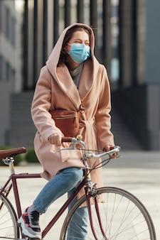 Giovane donna in maschera medica viso guida bicicletta