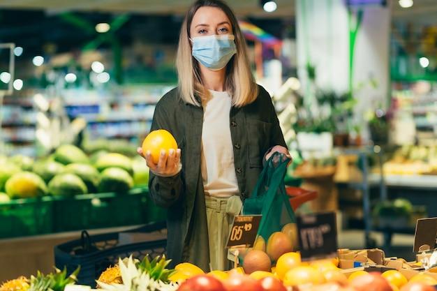 La giovane donna in maschera protettiva medica in faccia sceglie e raccoglie in eco-bag verdure o frutta al supermercato la donna in piedi in un mercato di alimentari vicino al bancone acquista in un pacchetto riutilizzabile