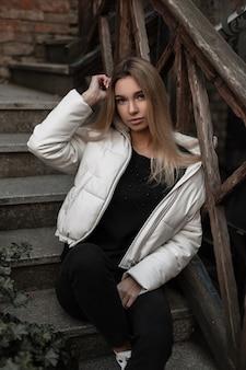 Giovane donna in una giacca bianca alla moda in un maglione nero all'aperto in città