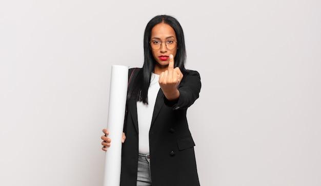 Giovane donna che si sente arrabbiata, infastidita, ribelle e aggressiva, lanciando il dito medio, contrattaccando