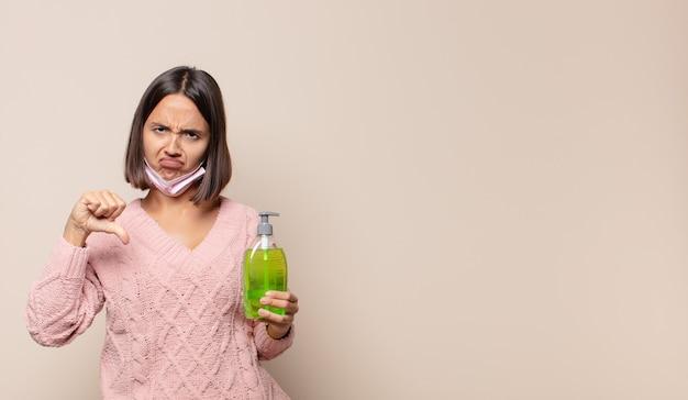 Giovane donna che si sente arrabbiata, arrabbiata, infastidita, delusa o scontenta, mostrando i pollici verso il basso con uno sguardo serio