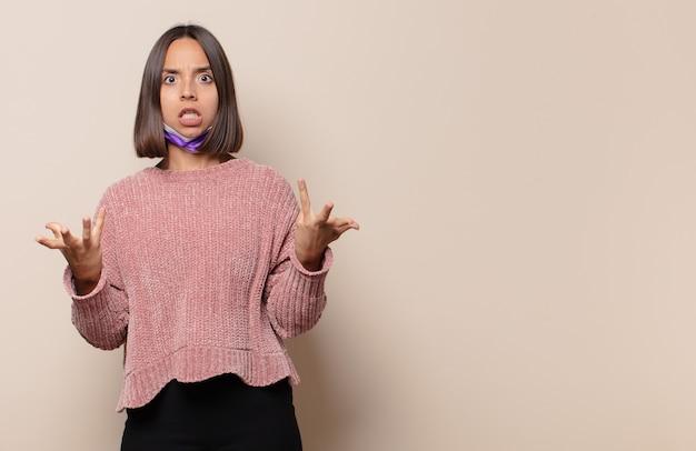 Giovane donna che si sente estremamente scioccata e sorpresa, ansiosa e in preda al panico, con uno sguardo stressato e inorridito