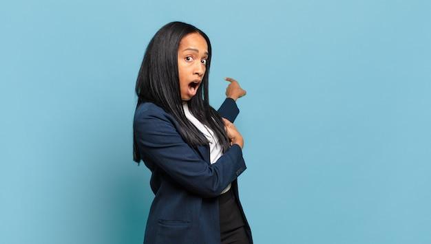 Giovane donna che si sente scioccata e sorpresa, indicando lo spazio di copia sul lato con uno sguardo stupito e a bocca aperta