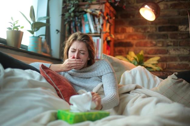 Giovane donna che si sente male - ragazza sdraiata sul divano, coperta di coperte, tosse con sensazione di vertigini