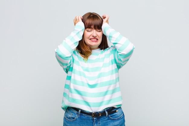 Giovane donna che si sente stressata e ansiosa, depressa e frustrata con un mal di testa, alzando entrambe le mani alla testa