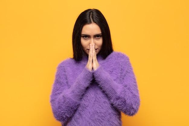 Giovane donna che si sente preoccupata, fiduciosa e religiosa, prega fedelmente con i palmi premuti, implorando perdono