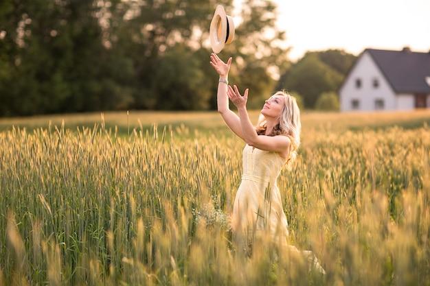 Una giovane donna nel campo lancia un cappello