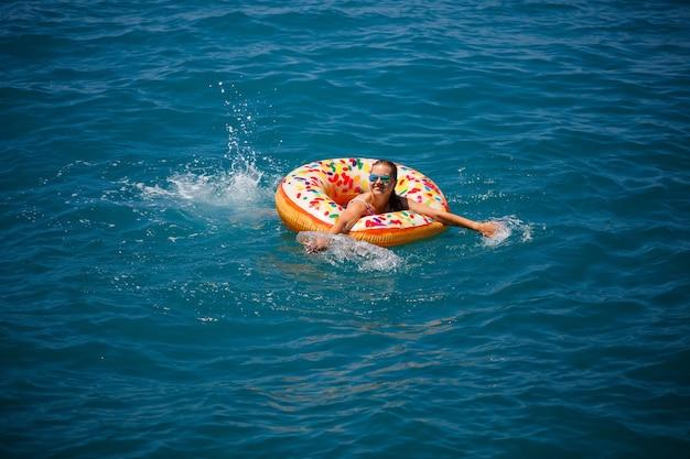 Giovane donna che galleggia su una grande ciambella gonfiabile nel mare turchese trasparente. vista di una donna snella rilassante in vacanza in turchia, egitto, mar mediterraneo.