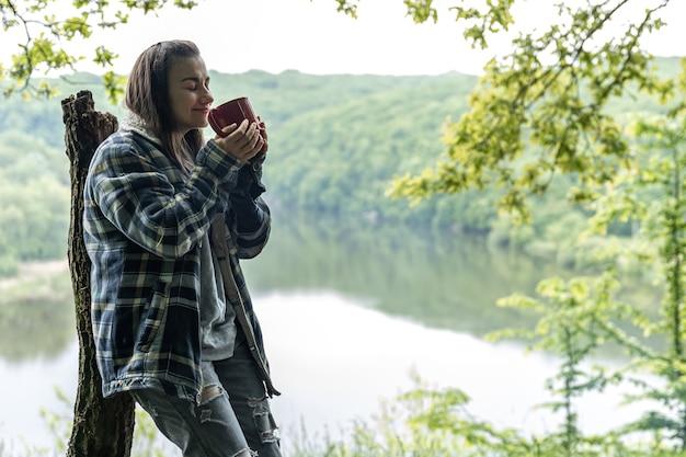 Una giovane donna nella foresta vicino al fiume si riscalda accanto al fuoco e beve una bevanda calda