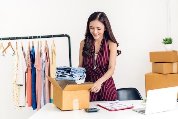 Giovane donna freelance che lavora pmi business shopping online e vestiti di imballaggio con scatola di cartone a casa -