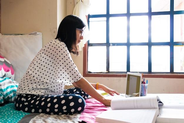 Una giovane donna da dietro che scrive sul suo laptop un documento, seduta sul letto con libri e penne nella sua camera da letto