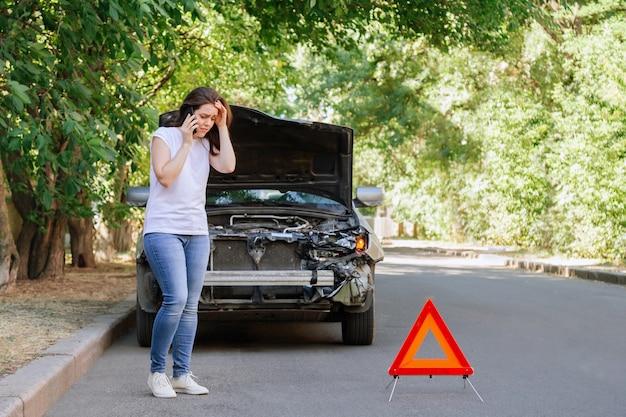 Giovane donna davanti alla macchina rotta in incidente d'auto. telefono donna che chiede aiuto e assicurazione dopo incidente d'auto sulla strada con segnale di stop del triangolo