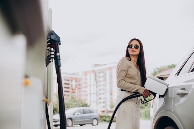 Giovane donna che rifornisce la sua auto Foto Premium