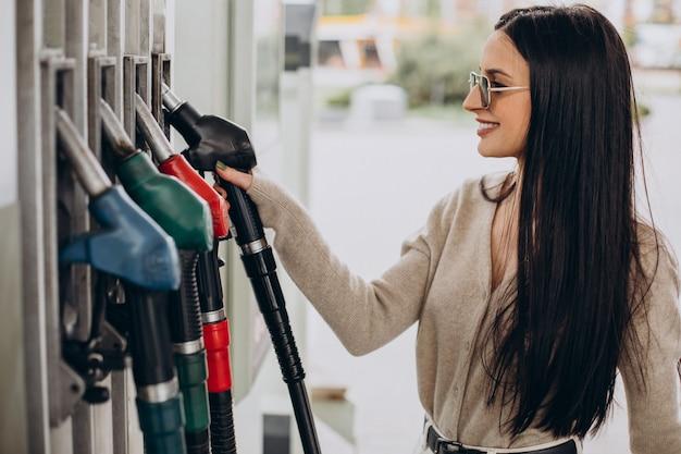 Giovane donna che rifornisce la sua auto