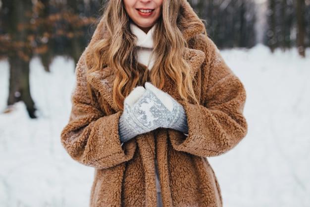 Giovane donna in pelliccia, guanti e sciarpa nel bosco innevato.