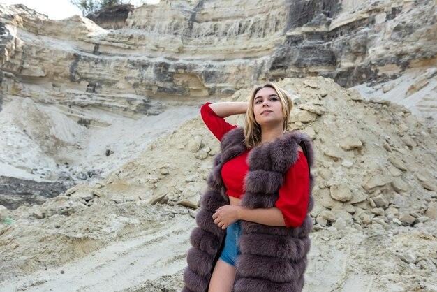Giovane donna in pelliccia posa in rocce di sabbia o canyon. vacanza, libertà