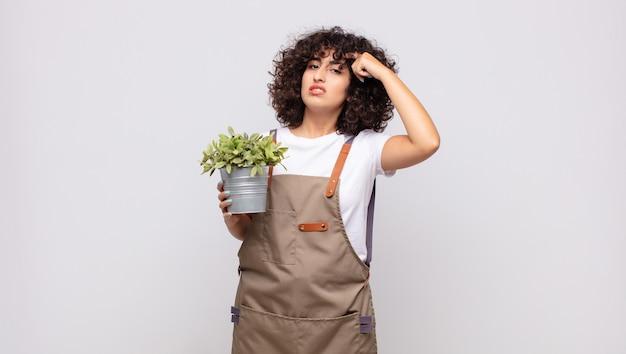 Giardiniere di giovane donna che si sente confuso e perplesso, dimostrando che sei pazzo, pazzo o fuori di testa