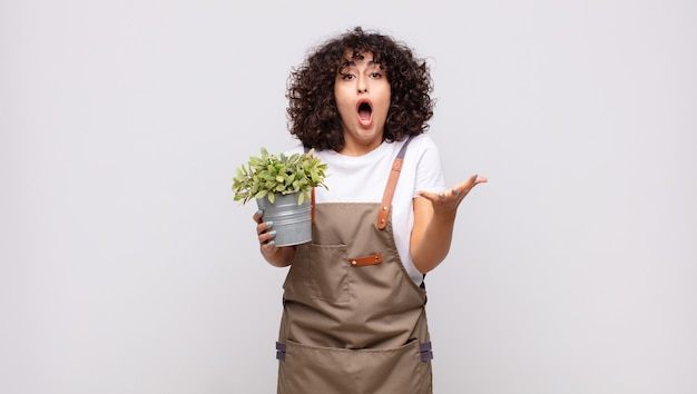 Giardiniere di giovane donna estremamente scioccato e sorpreso, ansioso e in preda al panico, con uno sguardo stressato e inorridito