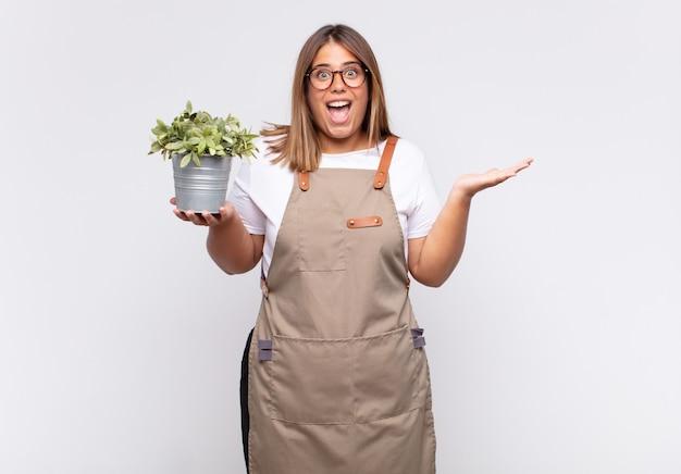 Giardiniere di giovane donna che si sente felice, eccitato, sorpreso o scioccato, sorridente e stupito per qualcosa di incredibile