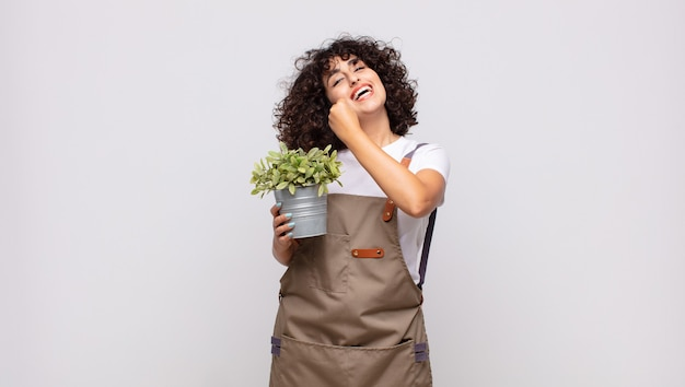 Giardiniere di giovane donna che si sente felice, positivo e di successo, motivato quando affronta una sfida o celebra buoni risultati