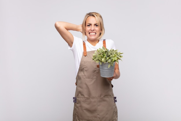 Giardiniere di giovane donna che si sente stressato, preoccupato, ansioso o spaventato, con le mani sulla testa, in preda al panico per errore