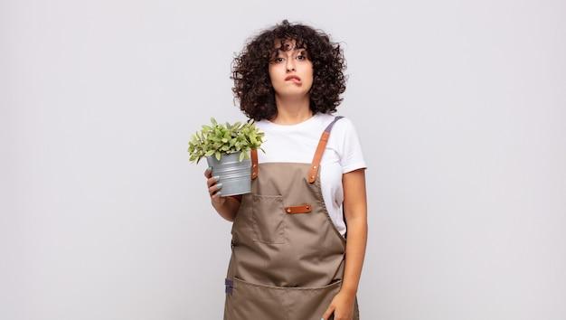 Giardiniere della giovane donna che sembra perplesso e confuso, mordendosi il labbro con un gesto nervoso, non conoscendo la risposta al problema