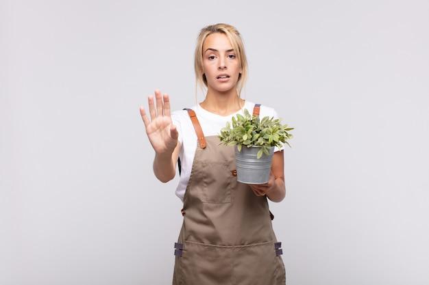 Giardiniere della giovane donna che sembra serio, severo, dispiaciuto e arrabbiato che mostra il palmo aperto che fa il gesto di arresto