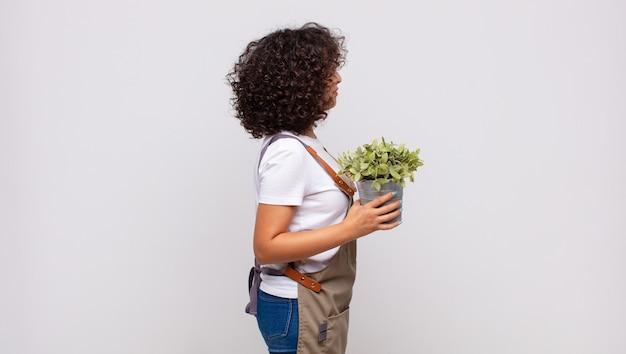 Giardiniere della giovane donna sulla vista di profilo che cerca di copiare lo spazio davanti, pensare, immaginare o sognare ad occhi aperti