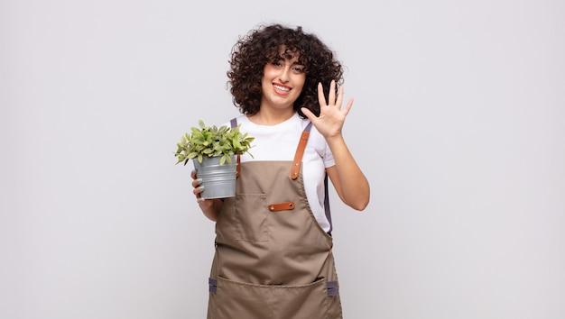 Giardiniere della giovane donna che sorride e che sembra amichevole, mostrando il numero cinque o quinto con la mano in avanti, conto alla rovescia