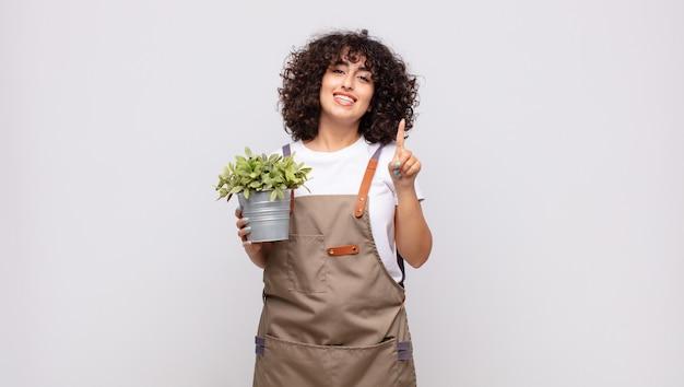 Giardiniere della giovane donna che sorride e che sembra amichevole, mostrando il numero uno o il primo con la mano in avanti, il conto alla rovescia