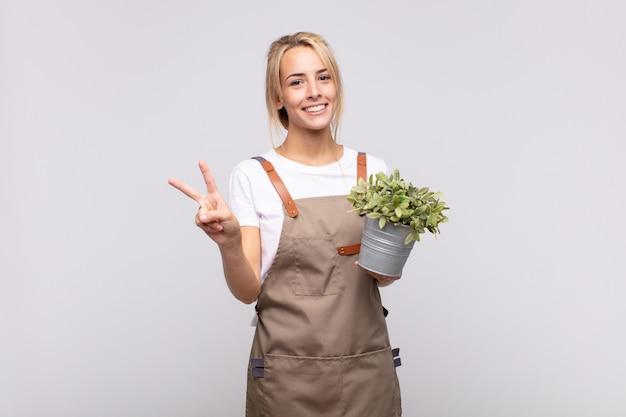 Giardiniere della giovane donna che sorride e che sembra amichevole, mostrando il numero due o il secondo con la mano avanti, conto alla rovescia