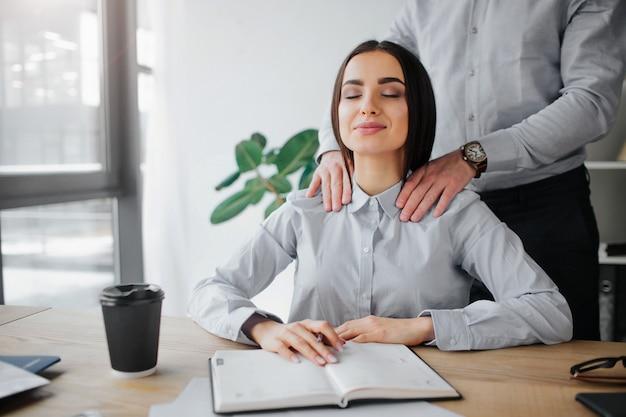 La giovane donna ottiene il massaggio alla spalla dal collega