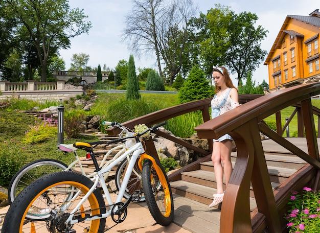 Giovane donna che scende sul ponte per andare in bicicletta nel bellissimo parco di lusso