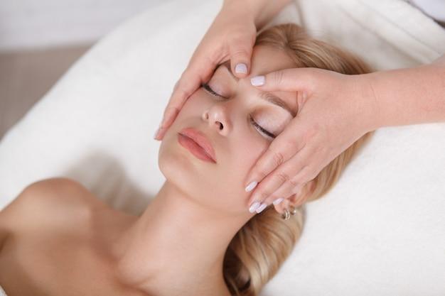 Giovane donna che ottiene un massaggio al viso