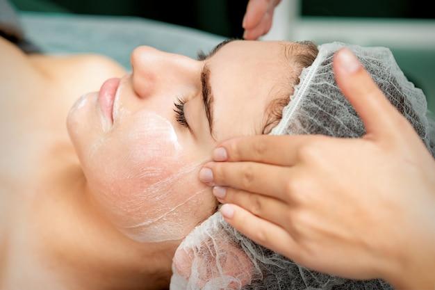 Giovane donna che ottiene massaggio facciale con gli occhi chiusi dall'estetista nel salone di bellezza