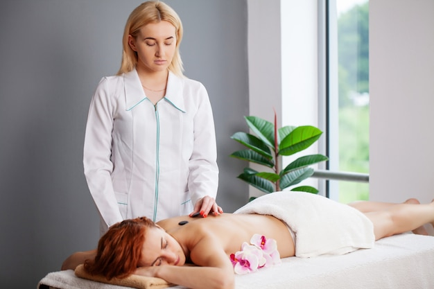 Giovane donna che ottiene massaggio con pietre calde nel salone della stazione termale.