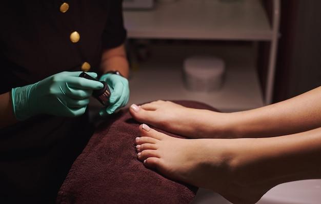 Giovane donna che ottiene pedicure professionale nel salone di bellezza. vista ritagliata delle mani del pedicurist e delle gambe della donna