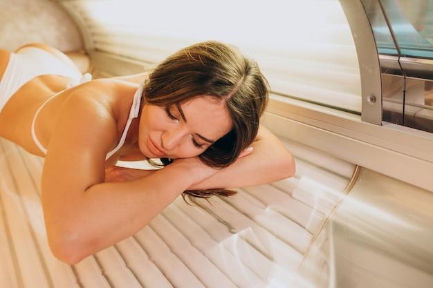 Giovane donna che si abbronza al solarium