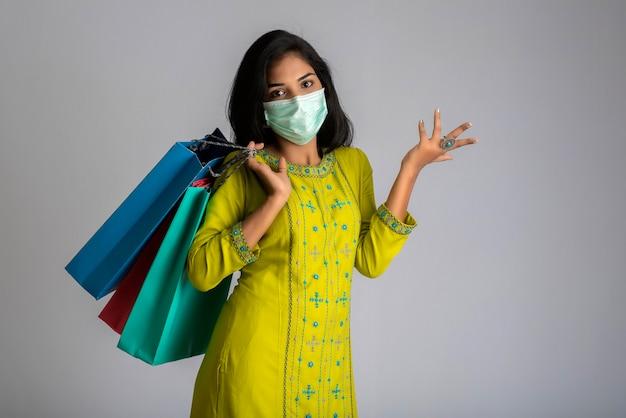 Ragazza della giovane donna che indossa la mascherina medica che tiene i sacchetti della spesa su fondo grigio. shopping concetto di vendita di sconto.