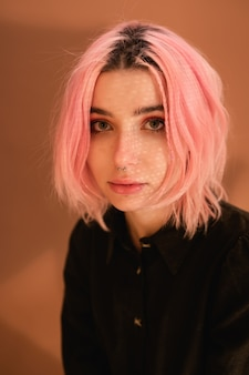 Ragazza della giovane donna con capelli rosa sul ritratto arancio dello studio del fondo della parete