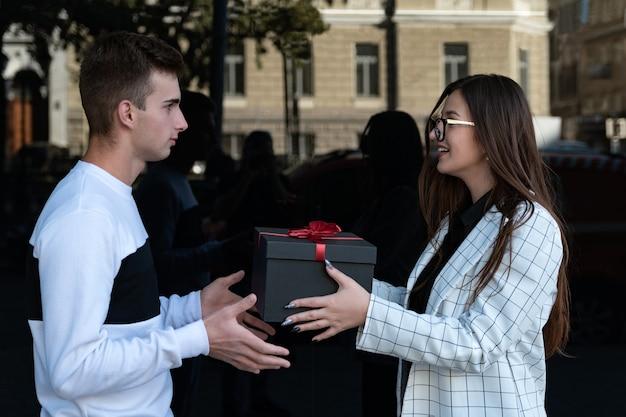 La giovane donna dà il regalo all'amante. la ragazza fa un regalo ad un amico.
