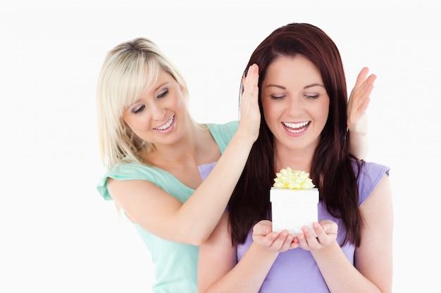 Giovane donna che dà un regalo alla sua amica