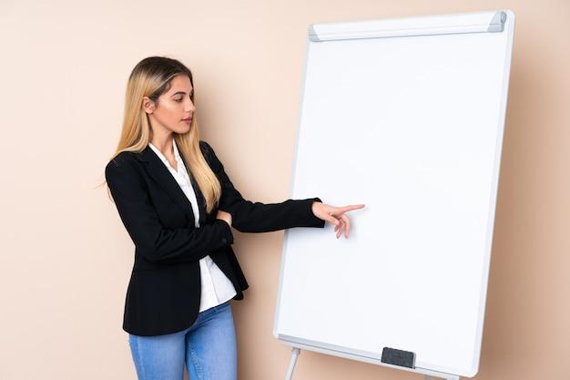 Giovane donna che dà una presentazione sul bordo bianco e che lo indica