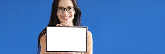 Giovane donna con gli occhiali in possesso di tablet digitale con schermo bianco nelle sue mani