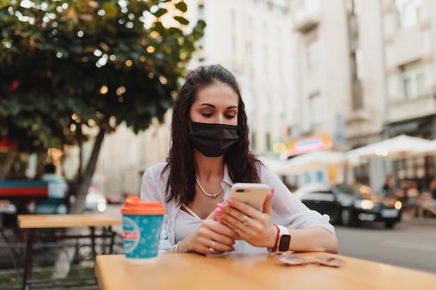 Giovane donna in occhiali e maschera utilizza il telefono. foto di alta qualità