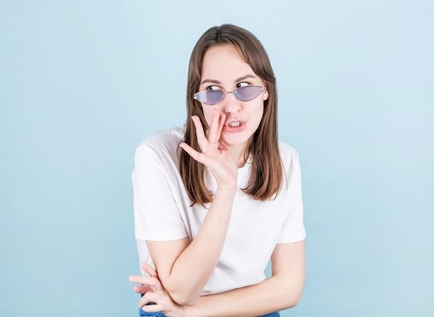 Giovane donna con gli occhiali che bisbiglia un segreto dietro la sua mano, su un blu